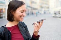 Giovane donna che usando assistente vocale ed inviando messaggio vocale fotografia stock libera da diritti