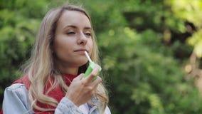 Giovane donna che usando condizione dello spruzzo della gola sui precedenti del parco Concetto igienico sanitario video d archivio