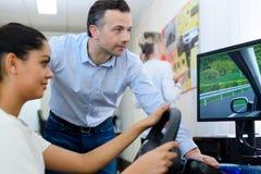 Giovane donna che usando guidando simulatore fotografie stock libere da diritti