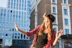 Giovane donna che usando i vetri alta tecnologia di realtà virtuale all'aperto Immagine Stock