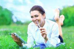 Giovane donna che usando l'erba mettente su all'aperto della compressa Fotografia Stock Libera da Diritti