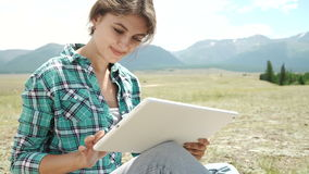 Giovane donna che usando l'erba mettente su all'aperto della compressa, sorridente archivi video