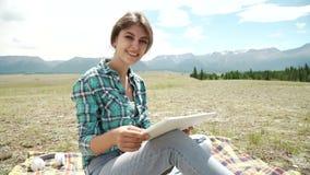 Giovane donna che usando l'erba mettente su all'aperto della compressa, sorridente stock footage