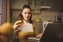 Giovane donna che usando la carta di credito e controllando le fatture immagini stock