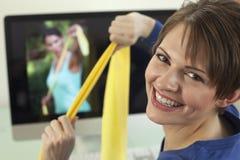 Giovane donna che usando le fasce di esercitazione Fotografie Stock Libere da Diritti