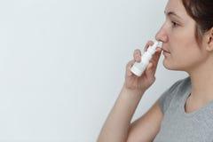 Giovane donna che usando le gocce di naso isolate su fondo bianco Fotografia Stock Libera da Diritti