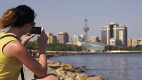 Giovane donna che usando Smartphone che si siede sull'argine vicino al mare ed ai grattacieli di Megapolis video d archivio