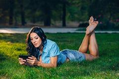 Giovane donna che usando stenditura all'aperto della compressa sull'erba Fotografia Stock Libera da Diritti