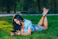 Giovane donna che usando stenditura all'aperto della compressa sull'erba Immagini Stock