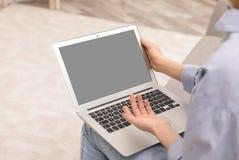 Giovane donna che usando video chiacchierata sul computer portatile a casa immagine stock