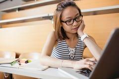 Giovane donna che utilizza computer portatile nell'aula Immagine Stock Libera da Diritti