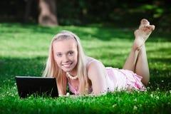 Giovane donna che utilizza computer portatile nella sosta Fotografie Stock