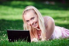 Giovane donna che utilizza computer portatile nella sosta Immagini Stock