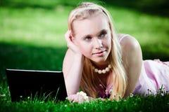 Giovane donna che utilizza computer portatile nella sosta Immagine Stock Libera da Diritti
