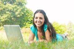 Giovane donna che utilizza computer portatile nella sosta Immagine Stock
