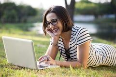 Giovane donna che utilizza computer portatile nella sosta Fotografia Stock Libera da Diritti