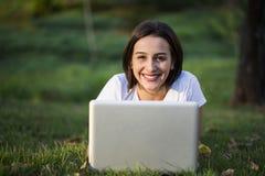 Giovane donna che utilizza computer portatile nella sosta Immagini Stock Libere da Diritti