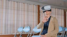 Giovane donna che utilizza i vetri di realtà virtuale nella sala per conferenze vuota archivi video