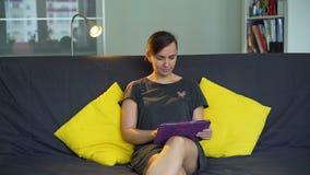 Giovane donna che utilizza il PC della compressa nel suo Appartement archivi video