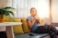 Giovane donna che utilizza il suo computer portatile nel salone immagini stock