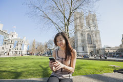 Giovane donna che utilizza telefono cellulare contro l'abbazia di Westminster a Londra, Inghilterra, Regno Unito Immagini Stock Libere da Diritti