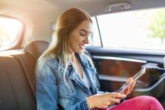 Giovane donna che utilizza una compressa in un'automobile immagini stock libere da diritti