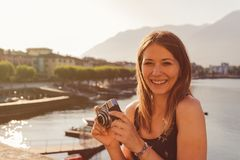 Giovane donna che utilizza una macchina fotografica d'annata davanti alla passeggiata del lago in Ascona immagine stock libera da diritti