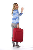 Giovane donna che va con una valigia rossa Fotografia Stock Libera da Diritti