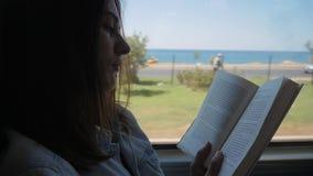 Giovane donna che viaggia dal bus e dal libro di lettura La ragazza sta viaggiando nell'automobile davanti alla finestra archivi video