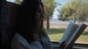 Giovane donna che viaggia dal bus e dal libro di lettura La ragazza sta viaggiando nell'automobile davanti alla finestra video d archivio