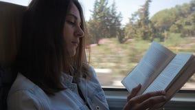 Giovane donna che viaggia dal bus e dal libro di lettura La ragazza sta viaggiando nell'automobile davanti alla finestra stock footage