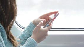 Giovane donna che viaggia in un treno e che per mezzo del telefono cellulare La mano femminile invia un messaggio dallo smartphon Immagini Stock Libere da Diritti