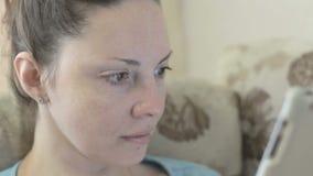 Giovane donna che websurfing sulla compressa a casa che sorride video d archivio