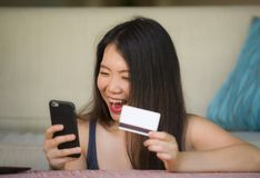 Giovane donna cinese asiatica felice e bella che tiene la carta di credito facendo uso del telefono cellulare per attività bancar fotografie stock libere da diritti