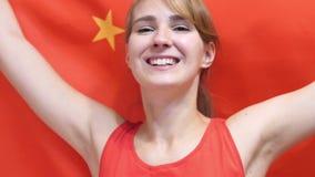 Giovane donna cinese che celebra mentre tenendo la bandiera cinese al rallentatore video d archivio