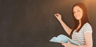 Giovane donna circa da scrivere su una lavagna che esamina la macchina fotografica Fotografia Stock