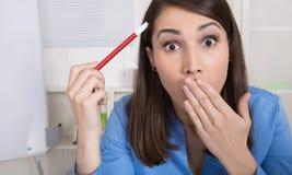 Giovane donna colpita e deludente di affari che tiene matita rossa Fotografie Stock