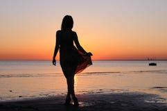 Giovane donna come siluetta dal mare Fotografie Stock Libere da Diritti