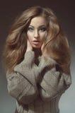 Giovane donna con bei capelli lunghi in lavorato a maglia in fotografia stock