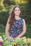 Giovane donna con bei capelli lunghi in vestito floreale vicino ai carretti di legno decorativi con i fiori, su un fondo di Fotografie Stock