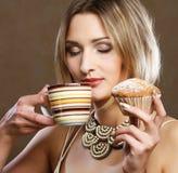 Giovane donna con caffè ed i biscotti fotografia stock
