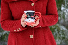Giovane donna con capelli biondi in cappotto rosso che tiene la tazza sveglia di festa del pupazzo di neve immagine stock libera da diritti