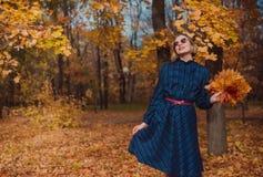 Giovane donna con capelli biondi che portano vestito blu che cammina nel parco di autunno fotografia stock