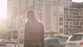 Giovane donna con capelli lunghi che cammina all'ufficio di affari nella vista posteriore della via della città archivi video