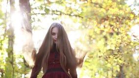Giovane donna con capelli lunghi su una natura di giorno elegante stock footage