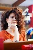 Giovane donna con capelli ricci lunghi allo studio dei capelli Fotografie Stock