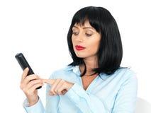 Giovane donna con capelli scuri che portano una camicia blu facendo uso di un telefono di Chordless Immagini Stock