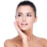 Giovane donna con crema cosmetica sul fronte Fotografie Stock Libere da Diritti