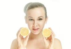 Giovane donna con due metà di un limone Fotografie Stock Libere da Diritti