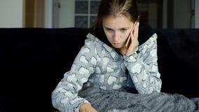 Giovane donna con febbre che chiama il suo medico stock footage